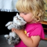 Little girl kisses kitten